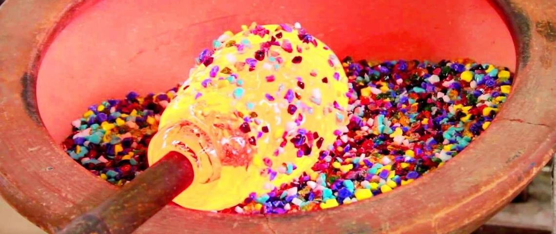 Du verre en fusion plongé dans des petites billes multicolores.