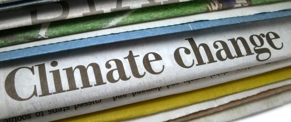Des journeaux papiers avec le titre changement climatique dessus.