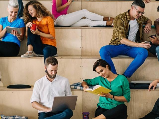 un groupe de gens assis sur une estrade de bois en train de regarder leur portable.