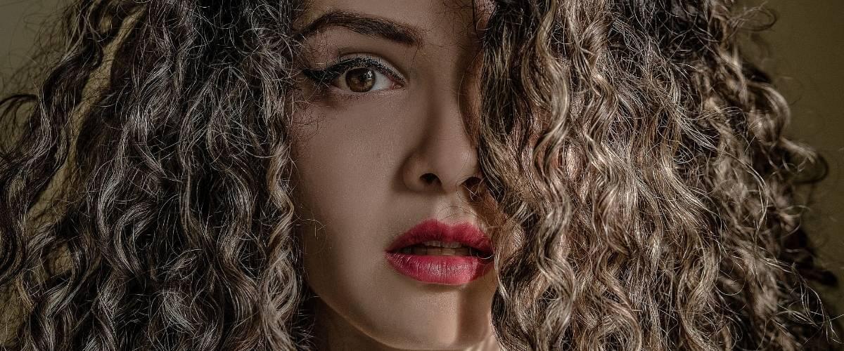 Le visage d'une femme avec les cheveux bouclés