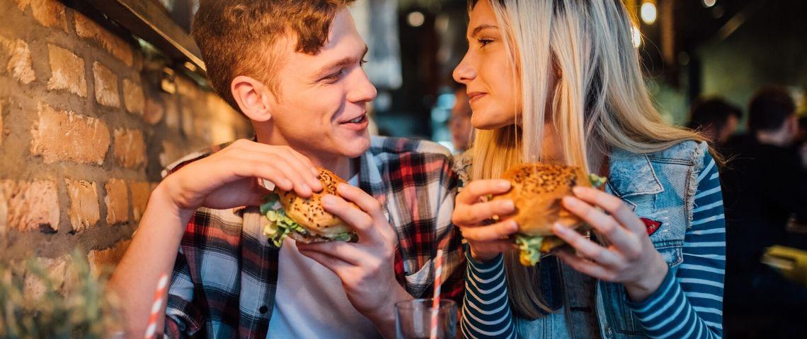 Un homme et un femme qui mangent un burger en se regardant