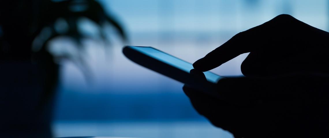 Main utilisant un smartphone dans l'ombre