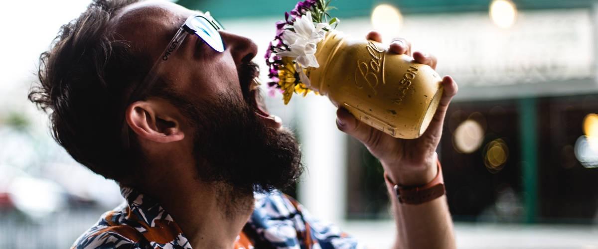 Un homme qui boit des fleurs dans un bocal