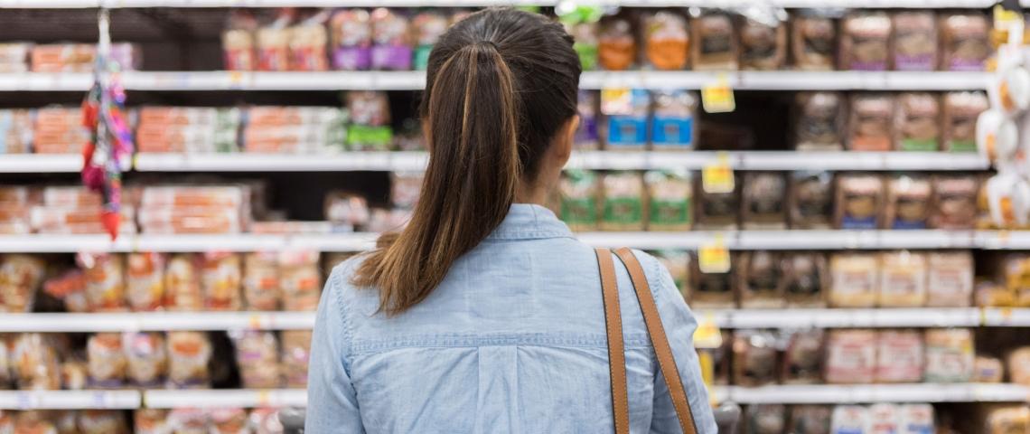 Une femme de dos regardant un rayon de supermarché