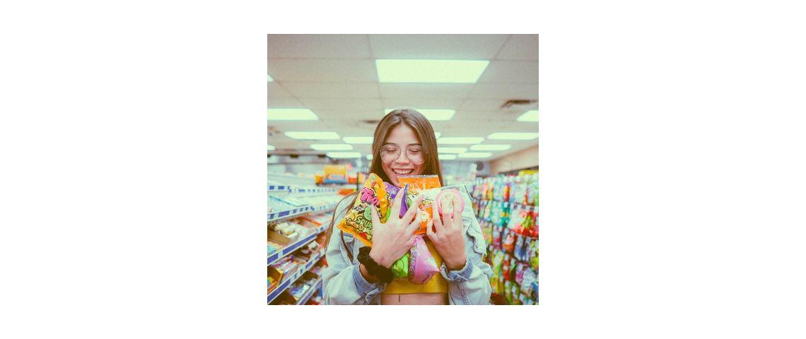 Visuel d'une femme au supermarché achetant de nombreuses sucreries