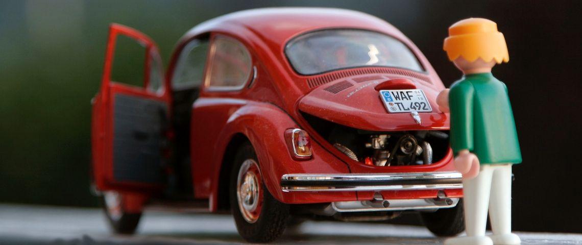 Un playmobile ouvre le coffre d'une voiture jouet