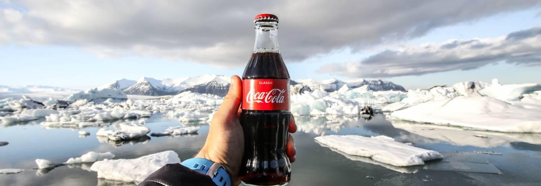 Bouteille de coca cola dans la main d'un homme devant la banquise