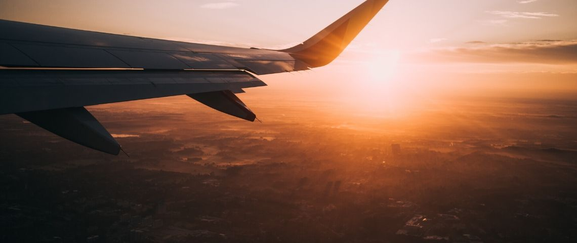 Phtot de l'aile d'un avion au soleil couchant