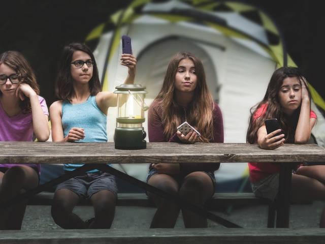 quatre jeunes filles assises à une table de camping qui regardent leur téléphone.
