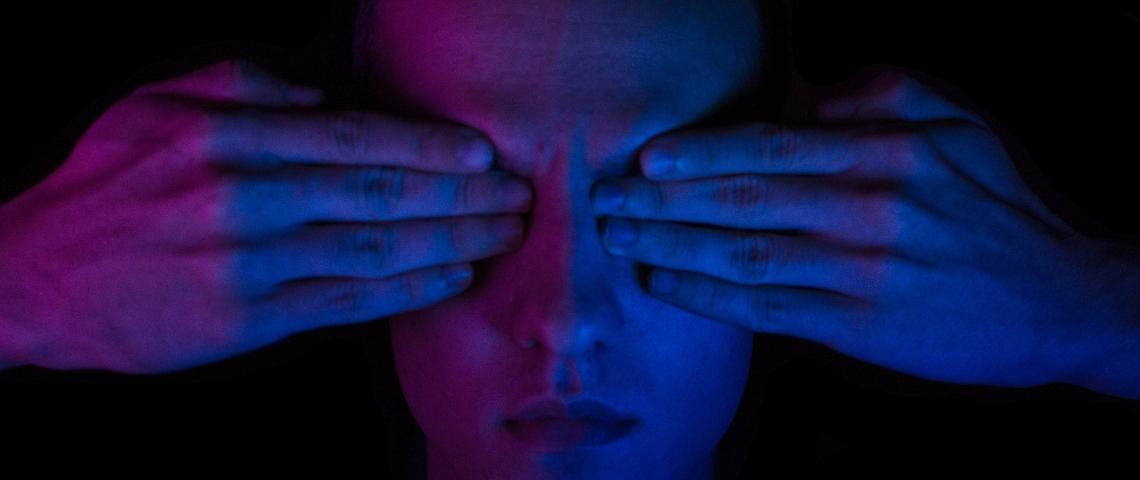 Une homme dans la pénombre avec ses deux mains sur les yeux. Bigup à tous les DV.