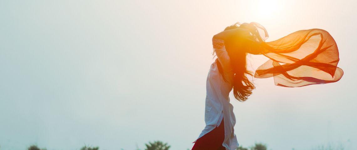 Viusle d'une femme les bras en l'air au soleil levant