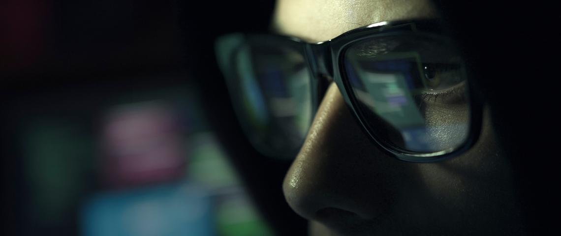 un gros plan sur un homme qui regarde un écran dans le noir