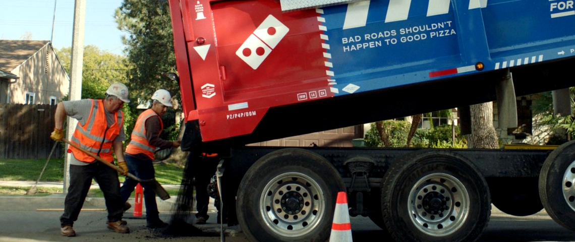 camion dominos pizza reconstruisant la route