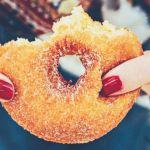 Les mains d'une femme qui tiennent un donut entamé