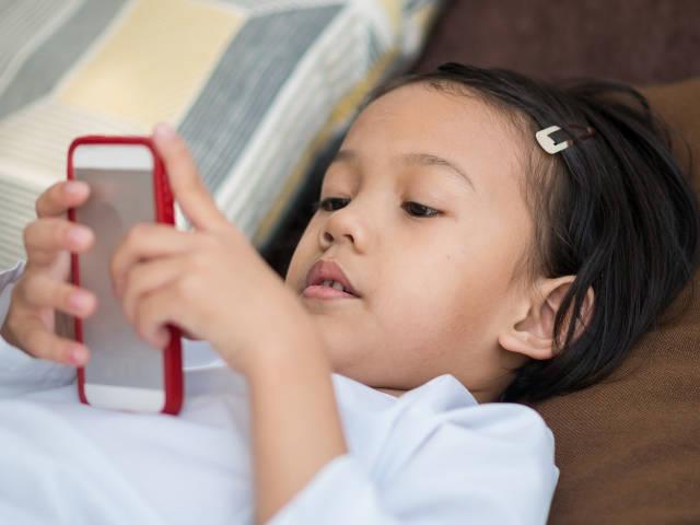 une petite fille asiatique devant son portable