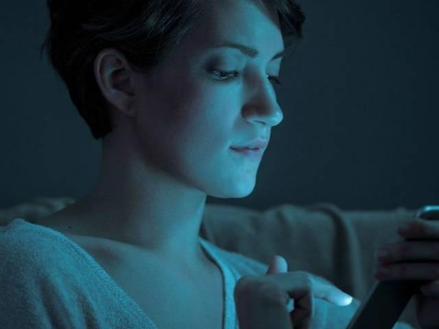Une femme qui regarde son écran de téléphone dans le noir