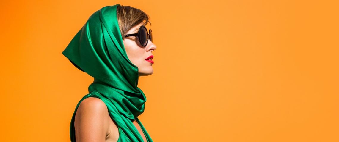 femme habillée en vert sur fond orange