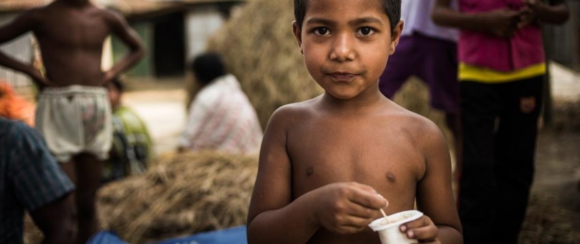 Un petit garçon au Bangladesh tenant un yaourt