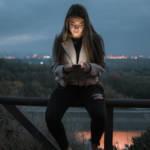 une jeune fille assise sur une barrière qui regarde son téléphone.