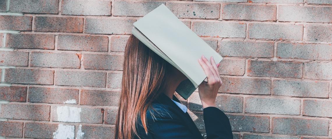 jeune femme masquant son visage avec un cahier
