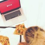 Une femme qui regarde Netflix en mangeant une pizza