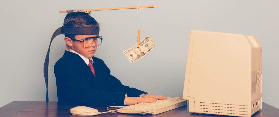 Petit garçon devant un ordinateur, tenté par un billet accroché devant ses yeux.