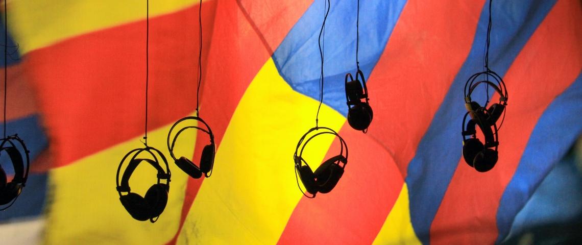 Des casques audio suspendu dans le vide avec un drat jaune rouge et bleu en arrière plan.