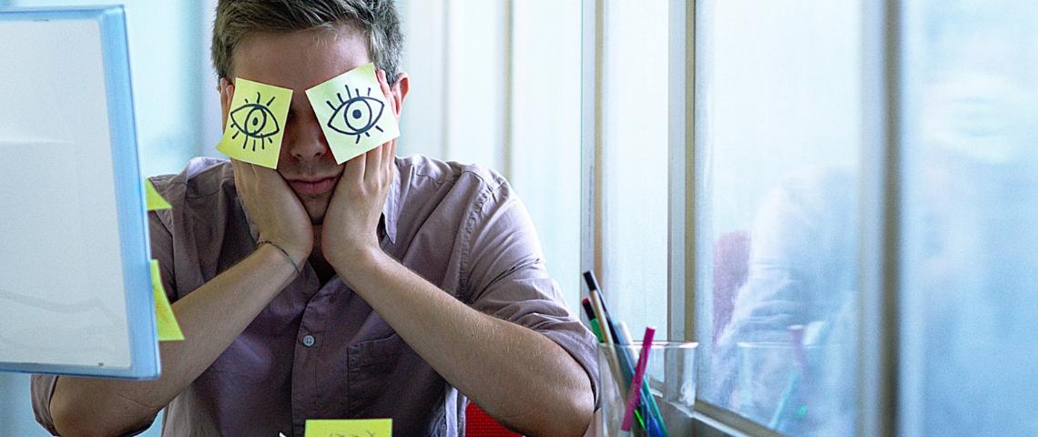 Un employé de bureau avec des post-it collés sur les yeux