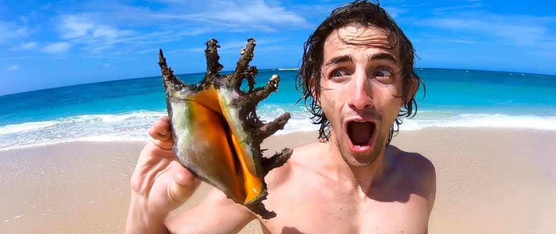 Un jeune homme sur une plage en train de tenir un coquillage