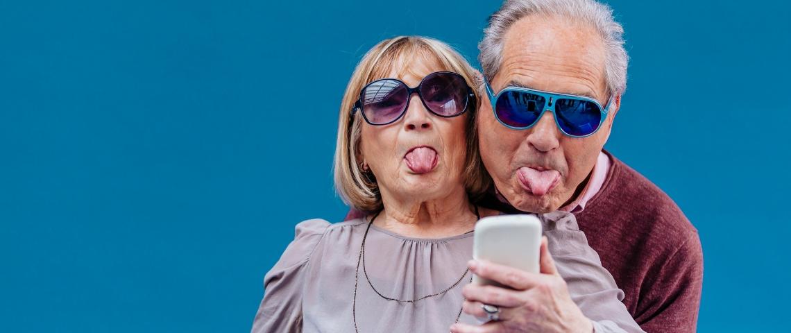 un couple de séniors tire la langue devant un smartphone