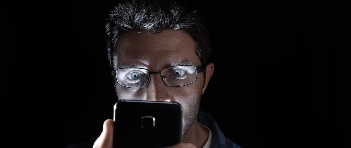 Homme regardant son smartphone de nuit