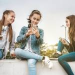 Trois jeunes filles sur un mur en train de regarder leur portable