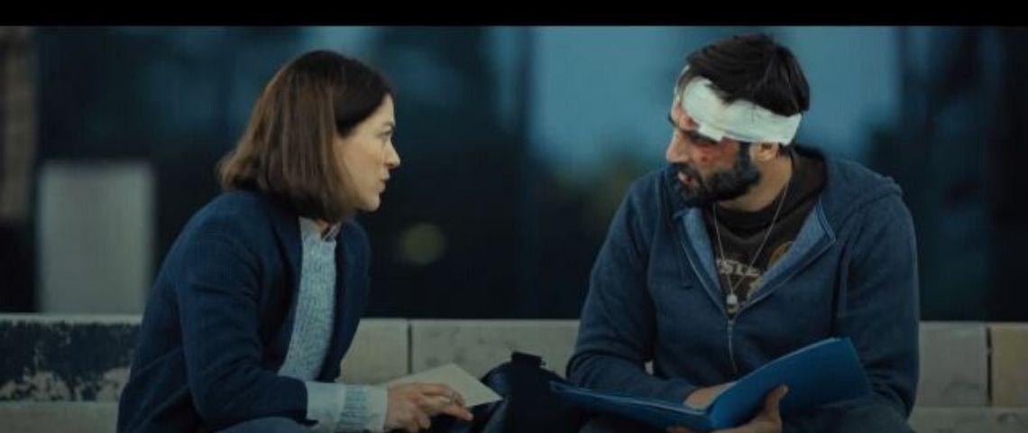 Une femme et un homme discutte assis sur un banc. L'homme a un bandage autour de la tête