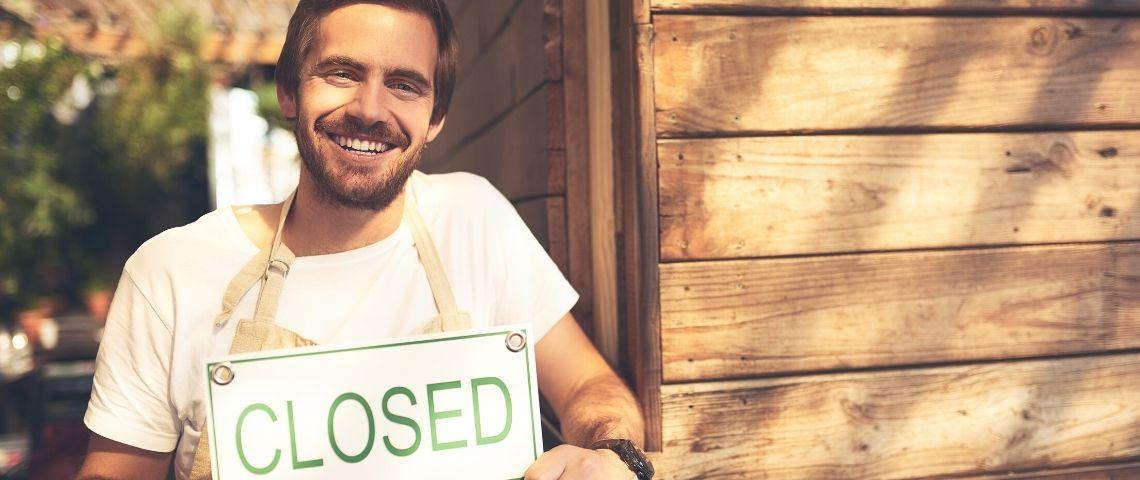 Un jeune homme souriant tient une pancarte de boutique  - fermé -