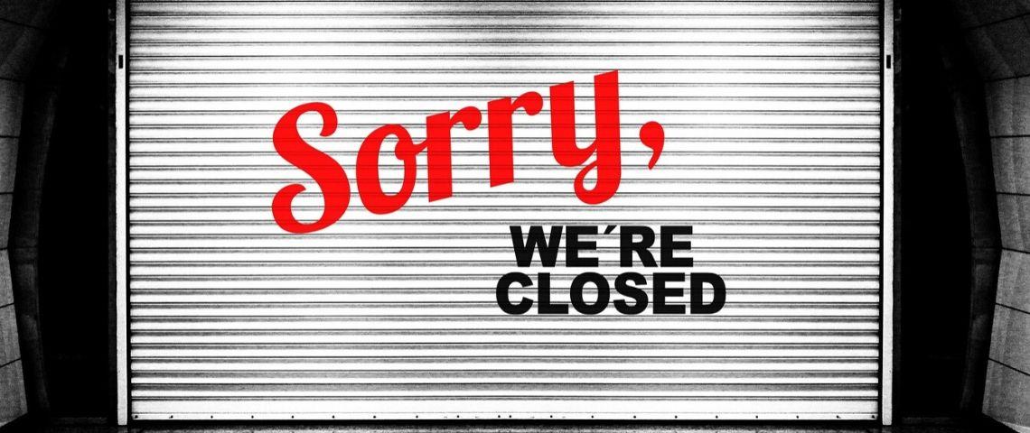 Rideau fermé d'une boutique avec le message : Sorry We're Closed