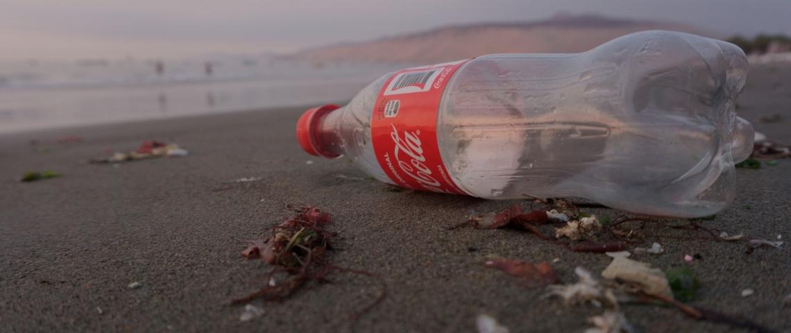 Une bouteille en plastique de Coca-Cola vide sur la plage