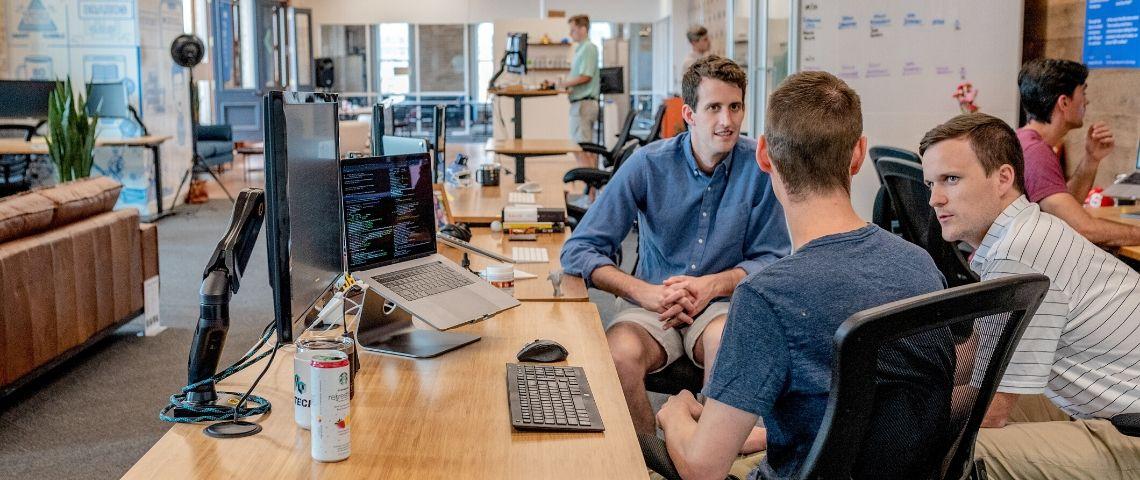 Trois parlent devant un ordinateur