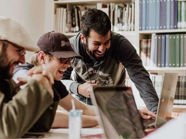 Des employés rient devant un ordinateur