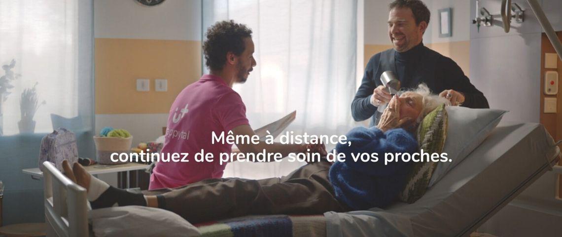 Homme assis sur un lit d'hopital en train de converser avec une femme agée pendant qu'elle se fait coiffer, le tout en riant