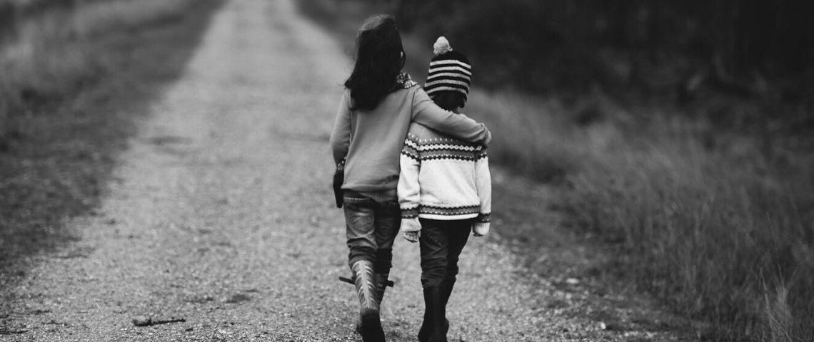 2 enfants de dos sur un chemin se tenant par l'épaule
