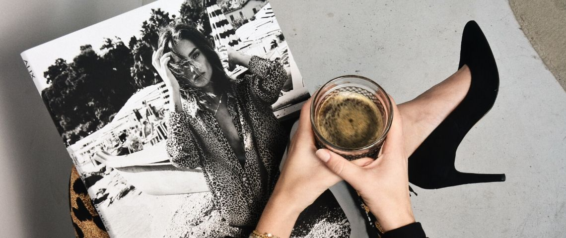 Une femme lit son magazine en tenant un café noir et porte des talons noirs