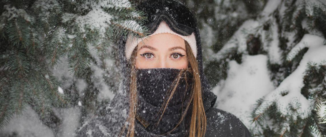 Une jeune femme porte un bonnet et une tenue de ski dans la neige