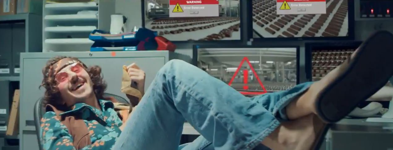 Capture d'écran de la vidéo : un technicien en mode hippie, les pieds sur son bureau