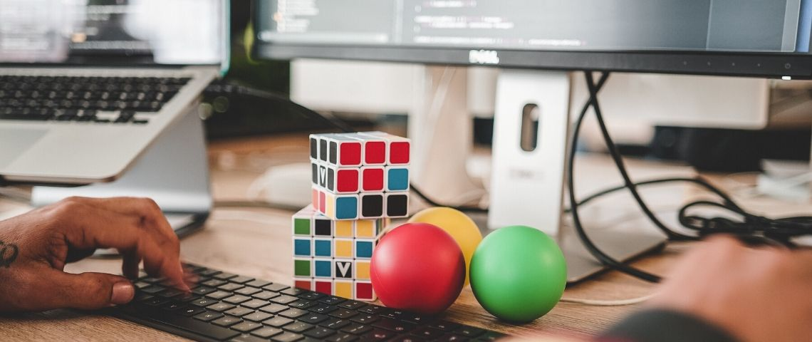 visuel d'un clavier avec 2 rubixcube et 3 balles de couleurs différentes posées devant le clavier