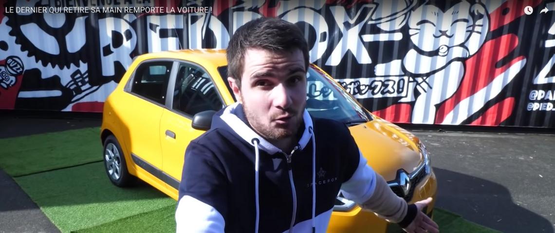 une jeune youtubeur devant une voiture jaune qui présente une vidéo de divertissement publicitaire