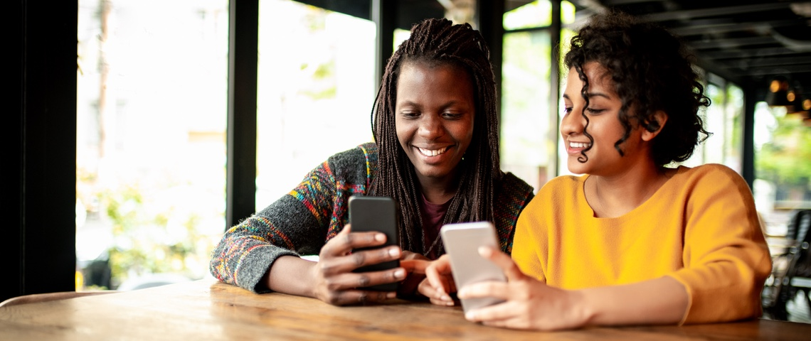 Deux femmes en train de s'échanger de l 'argent via une application smartphone.