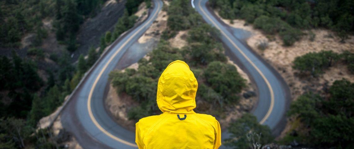Visuel d'un homme regardant une route sinueuse
