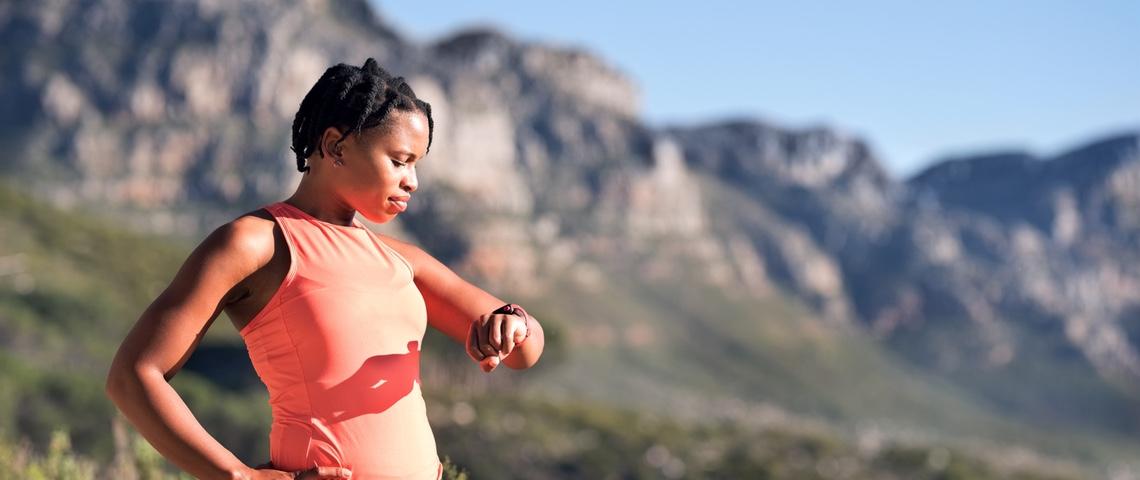 Femme en tenue de sport regarde son bracelet connecté dans la montagne.