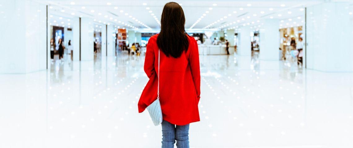 Une femme avec un manteau rouge de dos dans un centre commercial