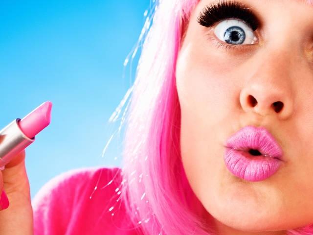 Une femme très maquillée portant une perruque rose et tenant un tube de rose à lèvres
